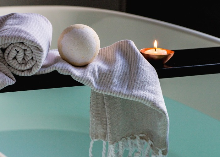 bathtub with candle, soap, washcloth