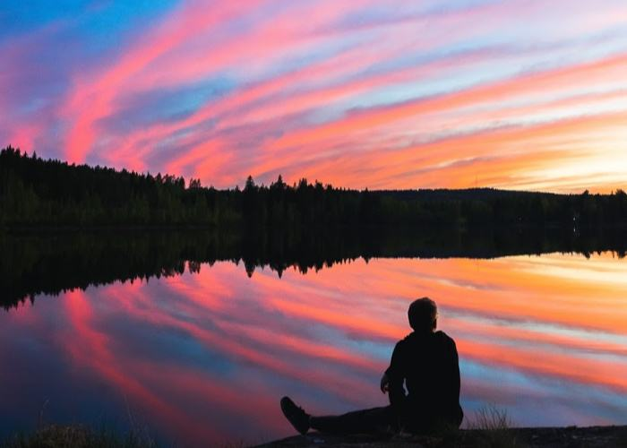 man sitting on a lake shore at sunset with rainbow sky reflection